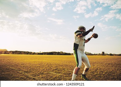 American football quarterback making a long throw during team practice on a sports field in the afternoon