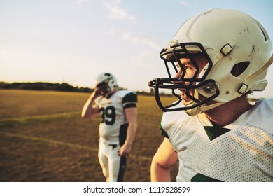 American football quarterback standing with a teammate on a grassy field on a sunny afternoon during a football game
