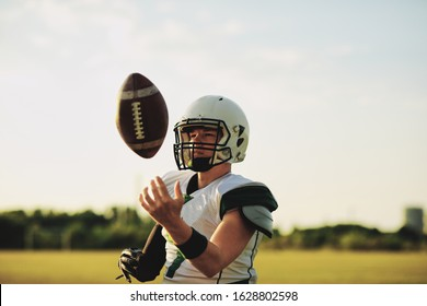 American football quarterback tossing a ball in the air during team practice on a sports field in the afternoon
