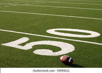 American football sitting on field next to 50 yard line.