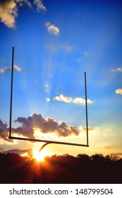 American football sport stadium goal posts in end zone over dramatic blue sky during a spectacular sunset