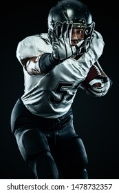 American football sportsman player in helmet isolated run in action on black background. Sport and motivation wallpaper. Team sports,