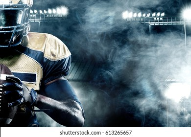 American football sportsman player on stadium with lights on background with copy space
