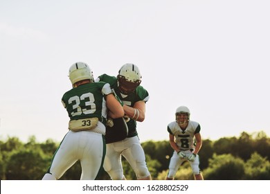 American football team doing defense and tackling drills together on a sports field during an afternoon practice