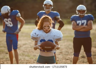American football woman player in action on the stadium. little red-haired girl with freckles plays sports of large and strong men in football on the field at sunset