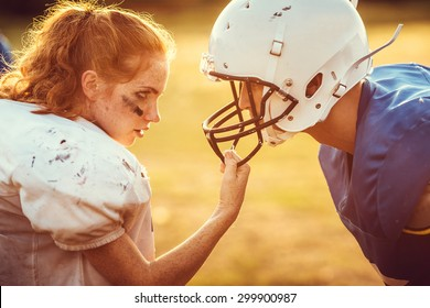 American football woman player in action on the stadium. little girl playing with big men in football on the field at sunset