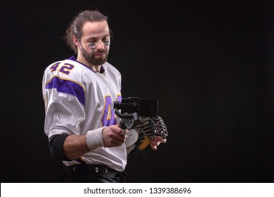 American footballer online in social networks using a mobile phone on the stabilizer from studio.