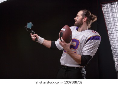 American footballer online in social networks using a mobile phone on the stabilizer.