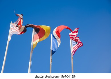 american, france, germany, and great britain countries flags waving in the wind against blue sky. windy weather.