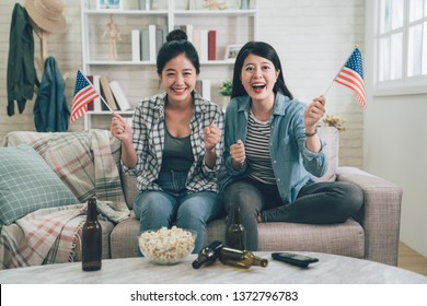 American friends watching football match on tv at home supporting favorite soccer team. two happy women smiling victory win holding usa flags sitting couch sofa with popcorn and bottle beer on table