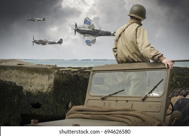 American GI on Normandy beach watches British Spitfire aircraft fly past from his vehicle