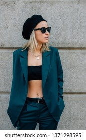 American girl in a jacket and black cap. Fashionable girl in a dark turquoise suit and sunglasses near the concrete wall. women's streetwear 2019. street style woman. how to dress this spring 2019