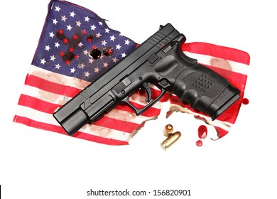 American Gothic Series/black automatic pistol laying upon burnt, blood-stained US flag with blood drops isolated alongside & two cartridges