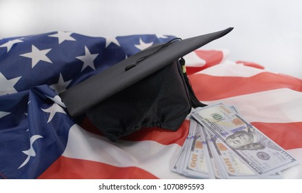 American graduation cap on United States flag with a pile of hundred dollar bills