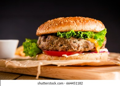 American hamburger with beef on dark background. American tasty food