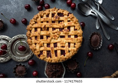 American homemade cherry pie on the table and chocolate muffins