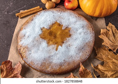 American homemade pumpkin or apple pie with walnut and autumn dry leaves on rustic table. Thanksgiving dish. Autumn harvest festival. Tonned