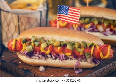 American hot dog with pickles,onions, ketchup, mustard and french fries at a Picnic for 4th of July