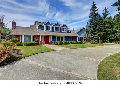 American house exterior with blue and white trim. Also red front door, well kept garden and driveway. Northwest, USA