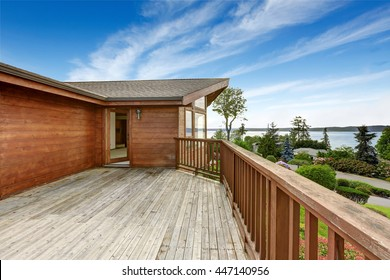American house with wooden walkout deck overlooking backyard and ocean