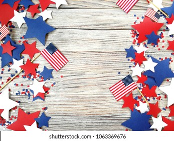 American independence Day, celebration, patriotism and holidays concept - flags and stars on the 4th of July party on top on wooden background