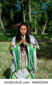 The American Indian against the blue sky in national clothes. Meditation. Worship of a deity. Leaving in a nirvana. Leader of the ancient tribe.