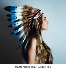 american Indian girl in a headdress of feathers.