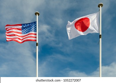 An american and japan flags are floating in a blue sky