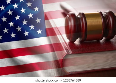 American justice and judiciary concept with a wooden judges gavel on a law book in court overlaid with the flag of the United States