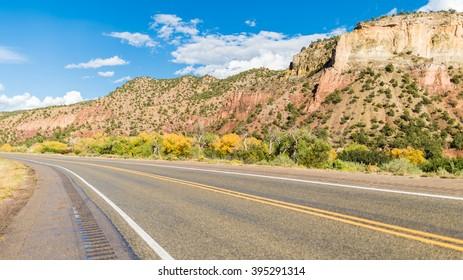 American landscape across long endless asphalt mountain road in beautiful sunny, Colorado, USA