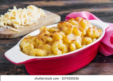 American macaroni dish Mac and Cheese in red and white baking form on wooden rustic table.