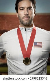 American male athlete smiling after winning a gold medal in a stadium. Sportsman with medal celebrating his victory.