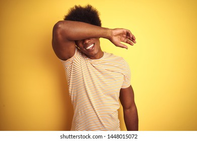 American man with afro hair wearing striped t-shirt standing over isolated yellow background covering eyes with arm smiling cheerful and funny. Blind concept.