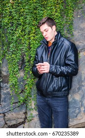 American man autumn/winter casual street fashion. Young handsome man wearing black leather jacket, standing by rocky wall with long green leaves in Central Park, New York, texting on cell phone.