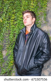 American man autumn/winter casual street fashion. Young handsome man wearing black leather jacket, standing by rock wall with long leaves at Central Park, New York, hands in pockets, thinking.