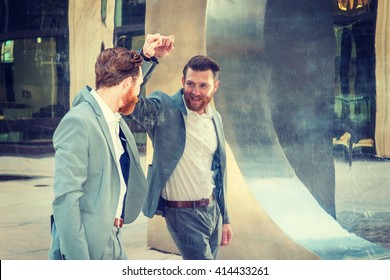 American Man with beard, mustache looking at mirror, wearing cadet blue suit, standing by metal mirror wall, looking at reflection. Concept of self assured, self esteem, self checking strategies.