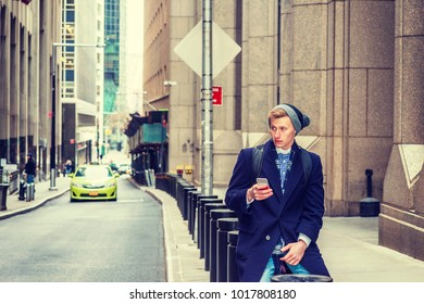 American man traveling in New York, wearing blue long overcoat, scarf, cuffed knit beanie hat, carrying back bag, sitting on vintage street, texting on cell phone. A small car on background.