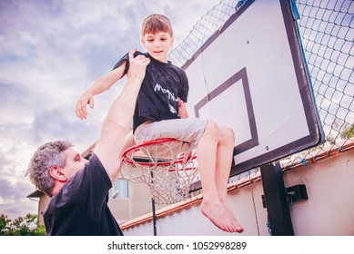 American March Madness - College Basketball Tournament mania. Very tall adult basketball player scores a young school boy in a basket on local playground. Happy childrens or fathers day concept image.