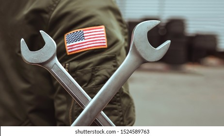 American mechanic holds a wrench on the background of the garage.  Auto repair concept.