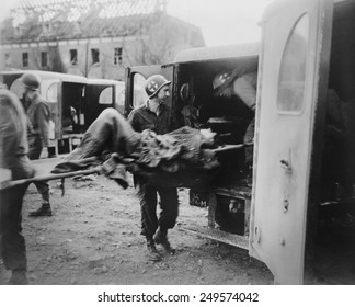 American medics place an almost-dead German slave laborer in an ambulance at Nordhausen. U.S. 3rd Army liberated the camp on April 12, 1945. Germany, World War 2.