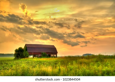 American Midwest Barn Landscape. Sunset over a farm field with a traditional red barn at the horizon.