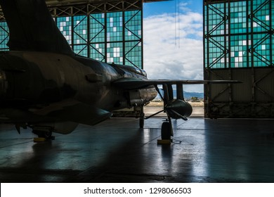 American military bomber aircraft with bombs parked in airport base hangar ready for flight attack