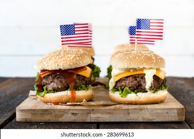 American mini beef burgers with cheese and USA flags on wooden board,selective focus