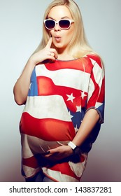 American Mom Concept: Surprised young pregnant woman in american flag like dress and trendy sunglasses posing over gray background. Hipster style. Studio shot