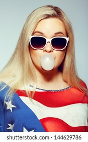 American Mom Concept: Young pregnant woman in american flag like dress and trendy sunglasses chewing bubble gum and posing over gray background. Hipster style. Close up. Studio shot