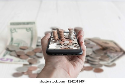 American money in the cellphone. Piles of cents and 5, 1 dollars banknotes on white background