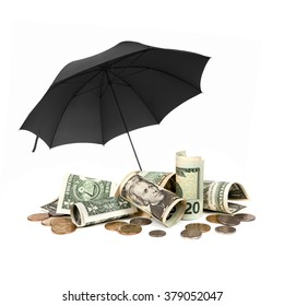 American money sheltered by black umbrella, over white background.  Includes notes and coins.