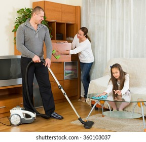 American mother, father and  girl doing general cleaning indoors