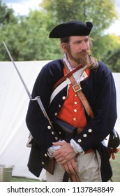 American Museum Bath UK 2002. An unidentified reenactor of the American Indian Wars wears the period uniform of a US Rebel. He stands holding a Flintlock Musket at a re-enactment event.