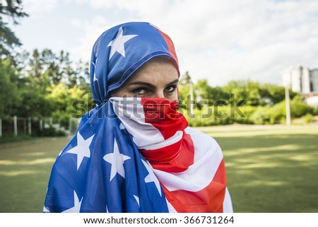 american muslim. flag of usa wrapped in the form of hijab. woman stand against green park and blue summer sky with clouds